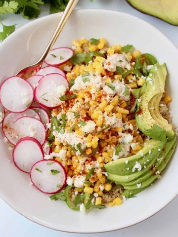 Corn, sliced radishes and avocado in a white bowl with a gold fork