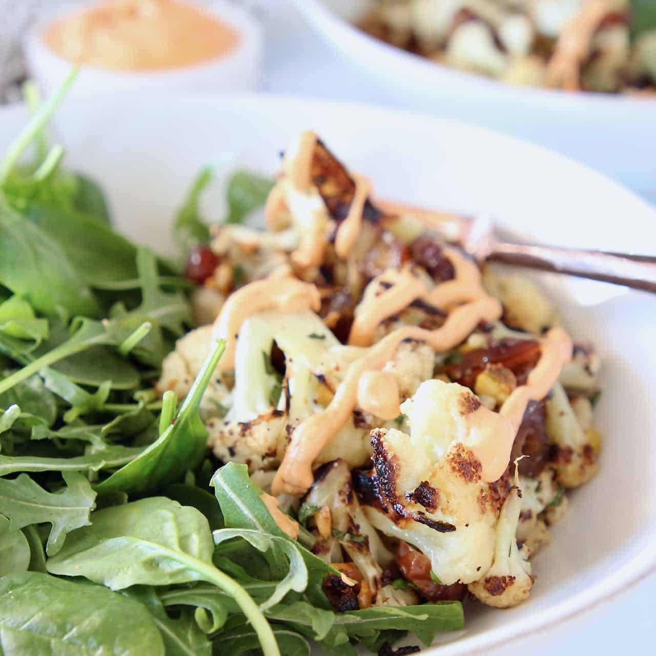 Charred cauliflower in bowl with arugula and chopped dates