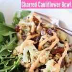 Cauliflower and arugula in bowl with fork