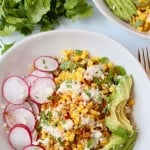 Overhead image of corn in bowl with sliced avocado and radishes