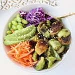 Overhead image of bowl with crispy brussels sprouts, carrots, avocado and cabbage