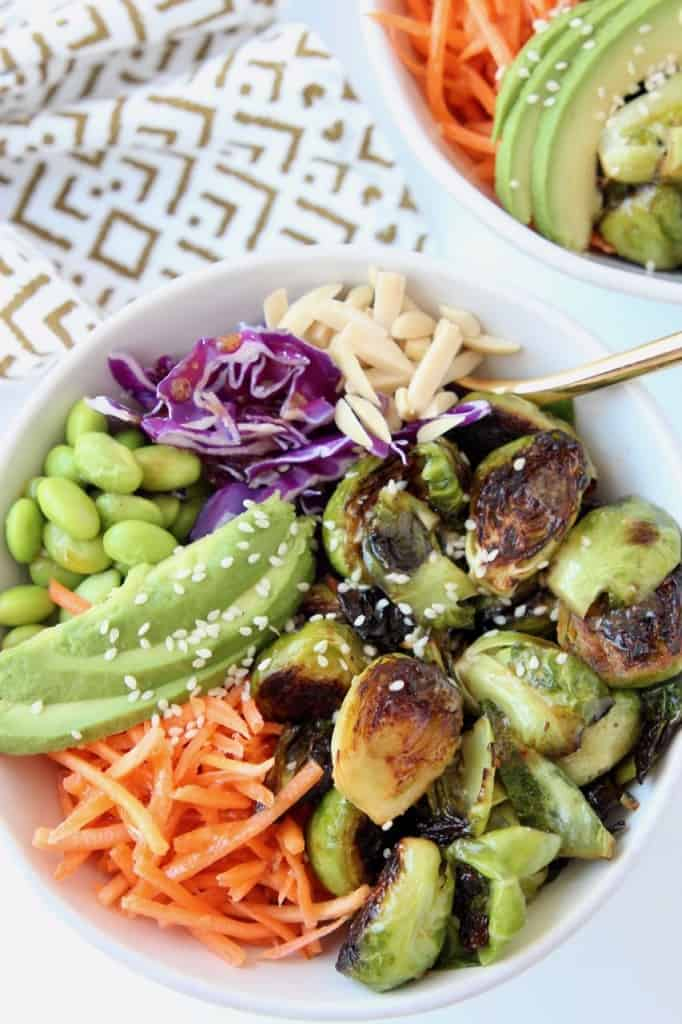 Overhead image of bowls filled with brussels sprouts, carrots, avocado and cabbage