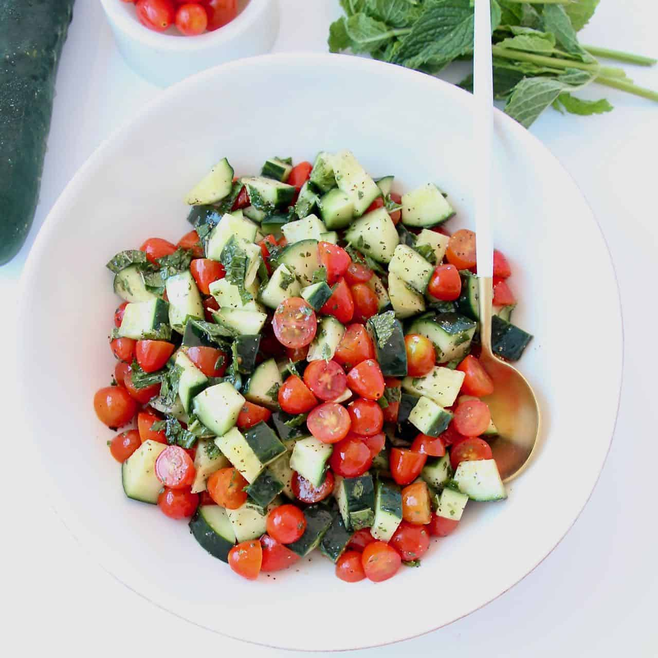 Diced cucumber tomato salad in bowl with spoon