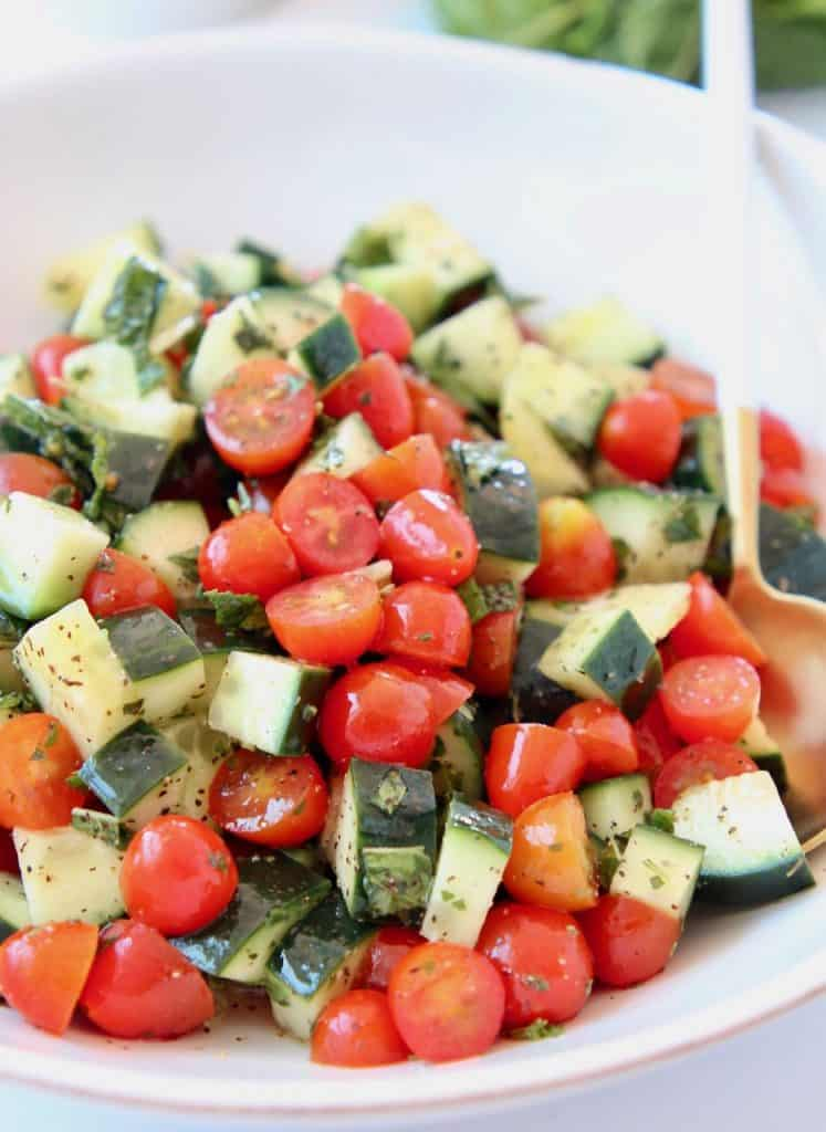 Diced cucumber tomato salad in white bowl with spoon