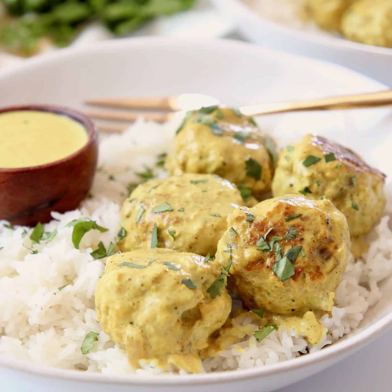 Meatballs in bowl with rice and yellow curry sauce