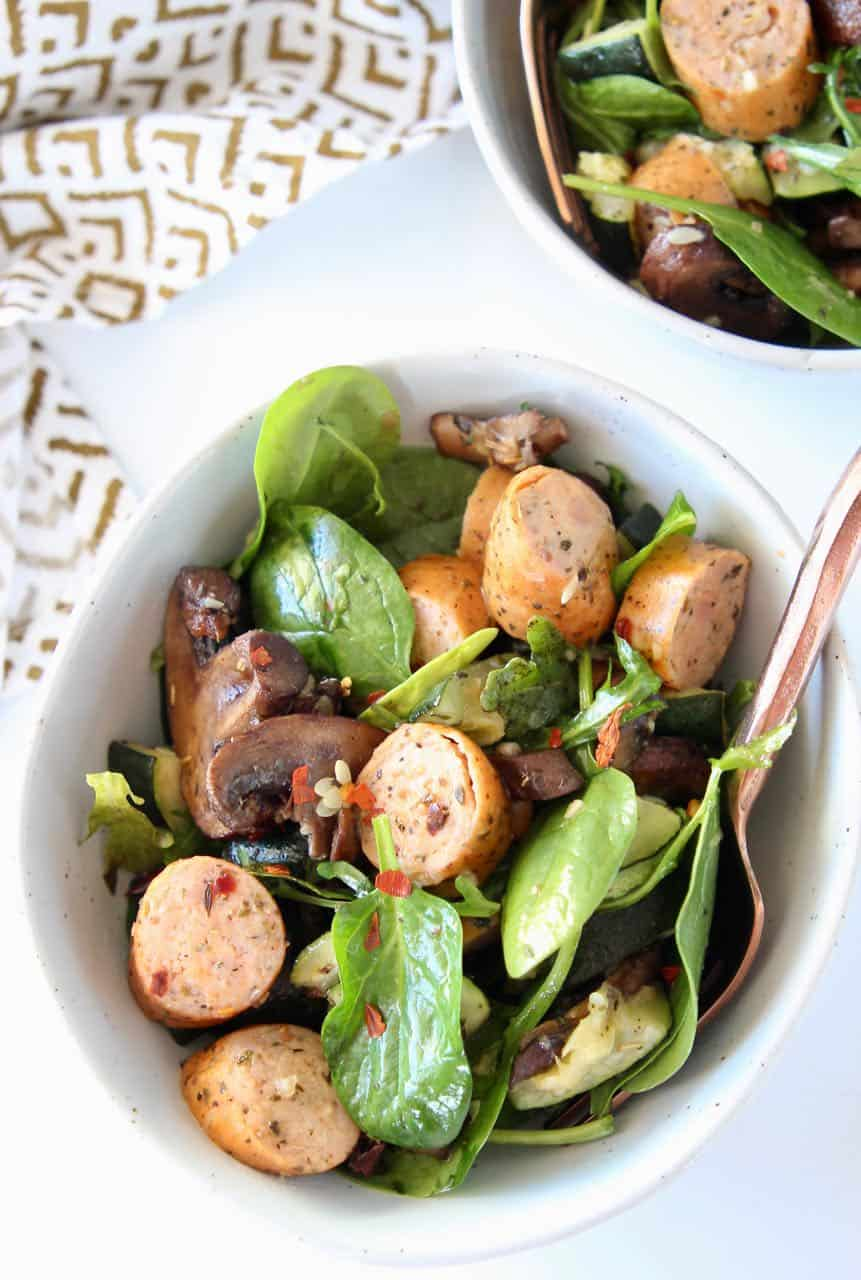 Slices of sausage in a bowl with spinach and mushrooms