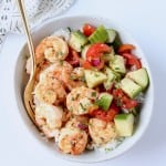 Overhead image of shrimp in bowl with tomato cucumber salad and a gold fork
