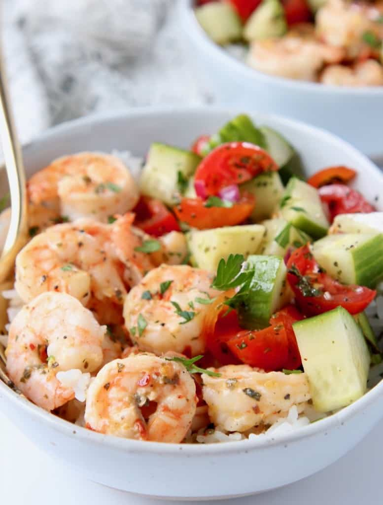 Shrimp in bowl with diced cucumber and tomato