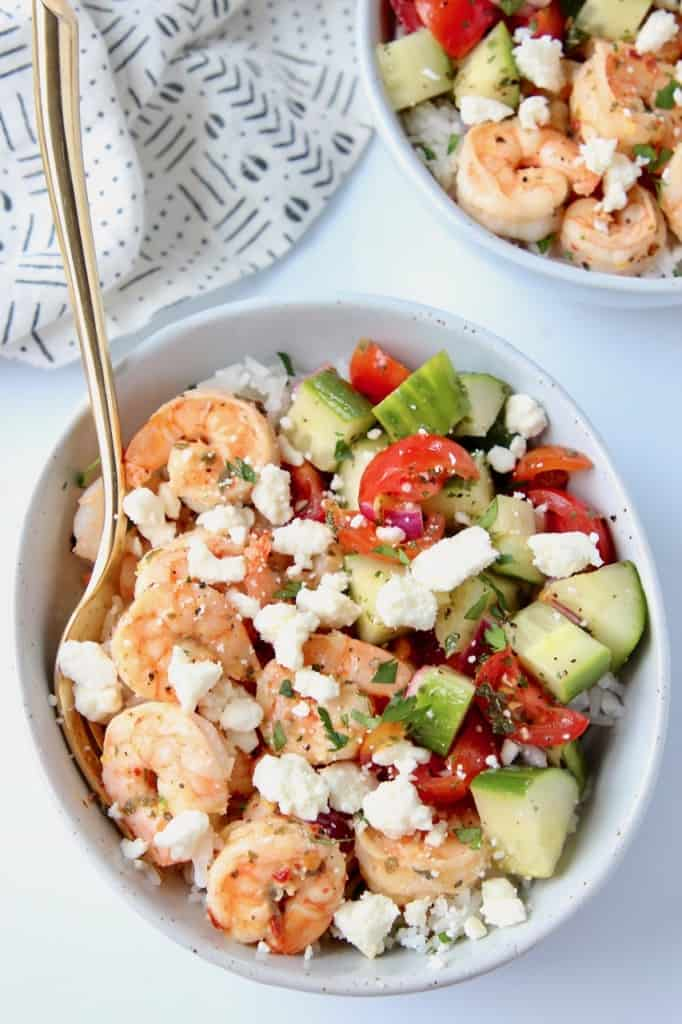 Cooked shrimp in bowl with tomato cucumber salsa, topped with feta cheese crumbles