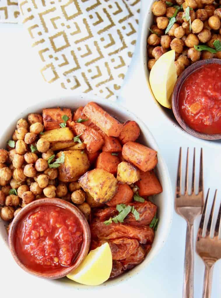 Overhead image of bowls filled with roasted chickpeas, carrots and tomatoes