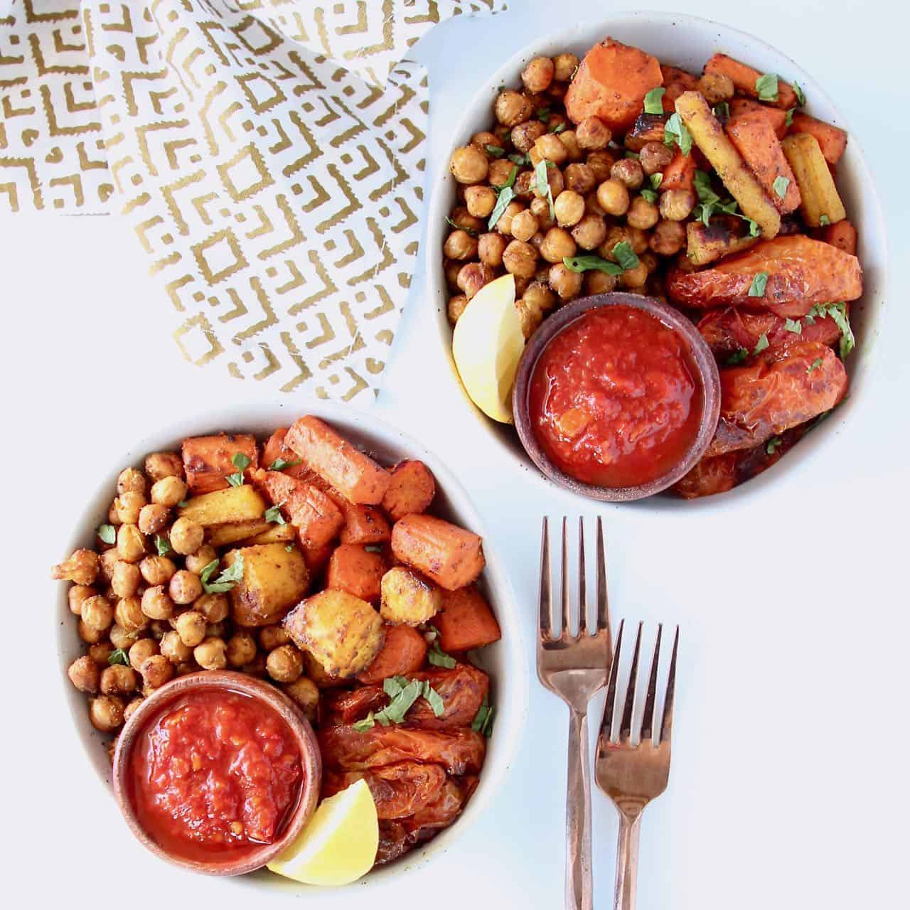 Overhead image of two bowls filled with chickpeas, carrots, tomatoes and lemon wedge