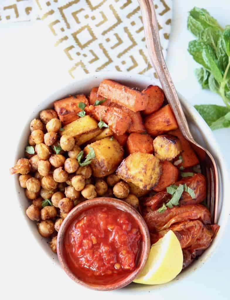 Overhead image of roasted chickpeas and carrots in a bowl with a small bowl of harissa sauce and lemon wedge
