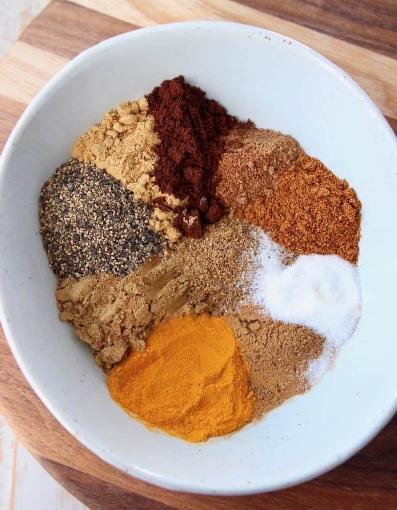 Various spices in a white bowl on a wood cutting board