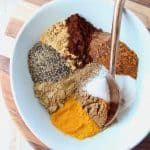 Spices in bowl with gold spoon