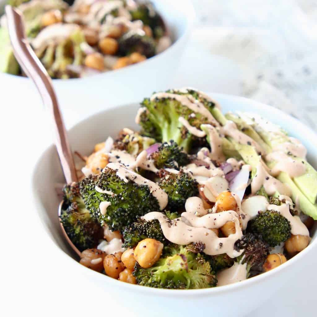 Roasted broccoli and chickpeas in bowl, drizzled with tahini sauce, with fork in bowl