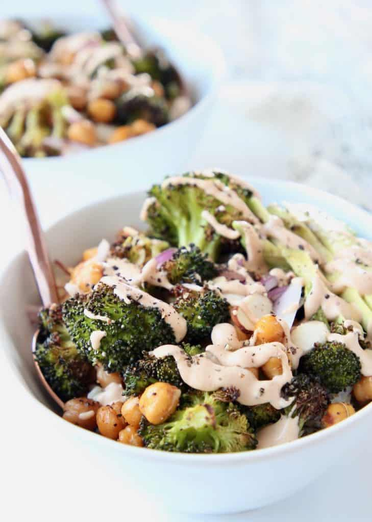 Roasted broccoli and chickpeas in white bowls with gold forks