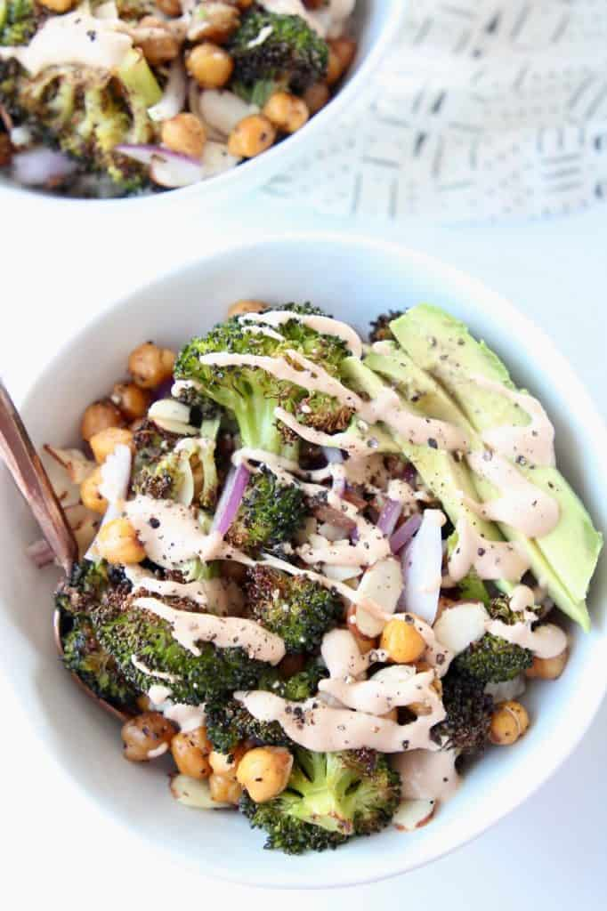 Roasted broccoli in bowls, topped with tahini dressing and avocado slices
