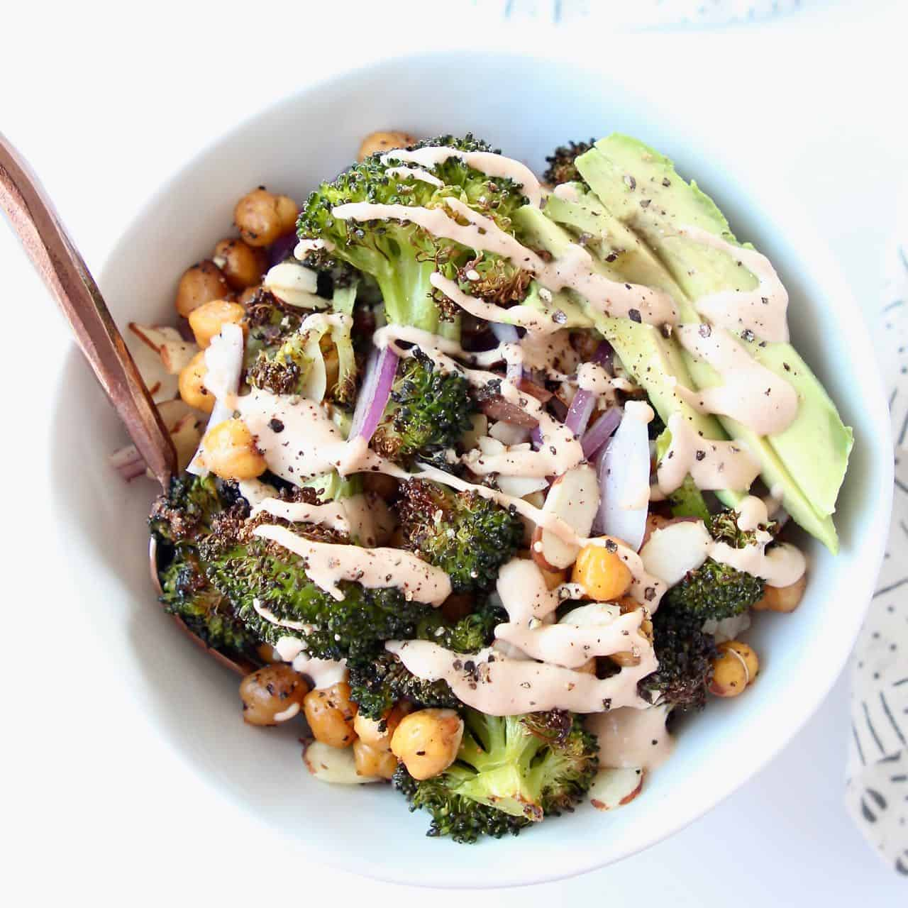 Overhead image of roasted broccoli and sliced avocado in bowl with fork