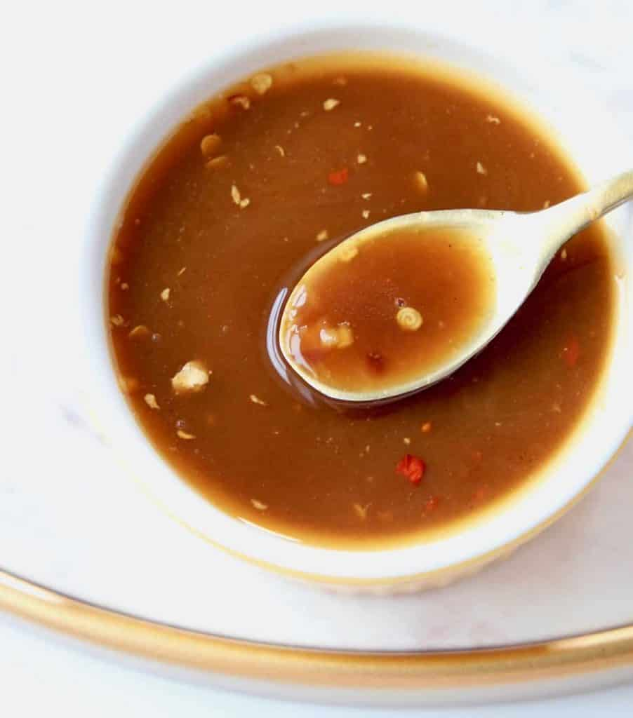 Overhead image of sesame sauce in bowl with gold spoon of sauce coming out of the bowl
