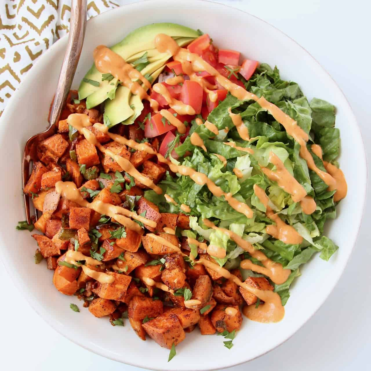 Overhead image of roasted sweet potatoes in bowl drizzled with creamy chipotle sauce