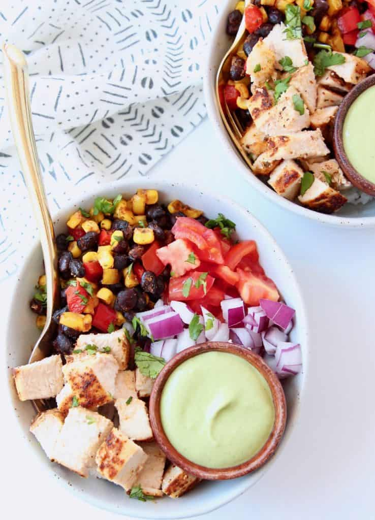 Overhead image of bowl with diced chicken, beans, corn, tomatoes and small bowl of avocado dressing