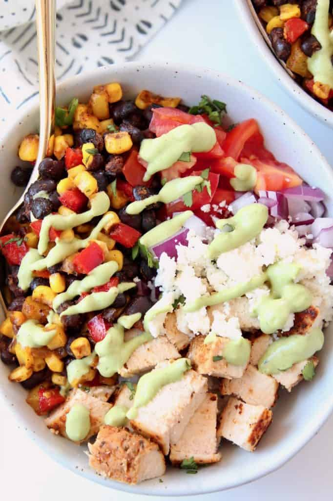 Bowl filled with diced chicken, black beans and corn, cheese and diced tomatoes, with gold fork in the bowl