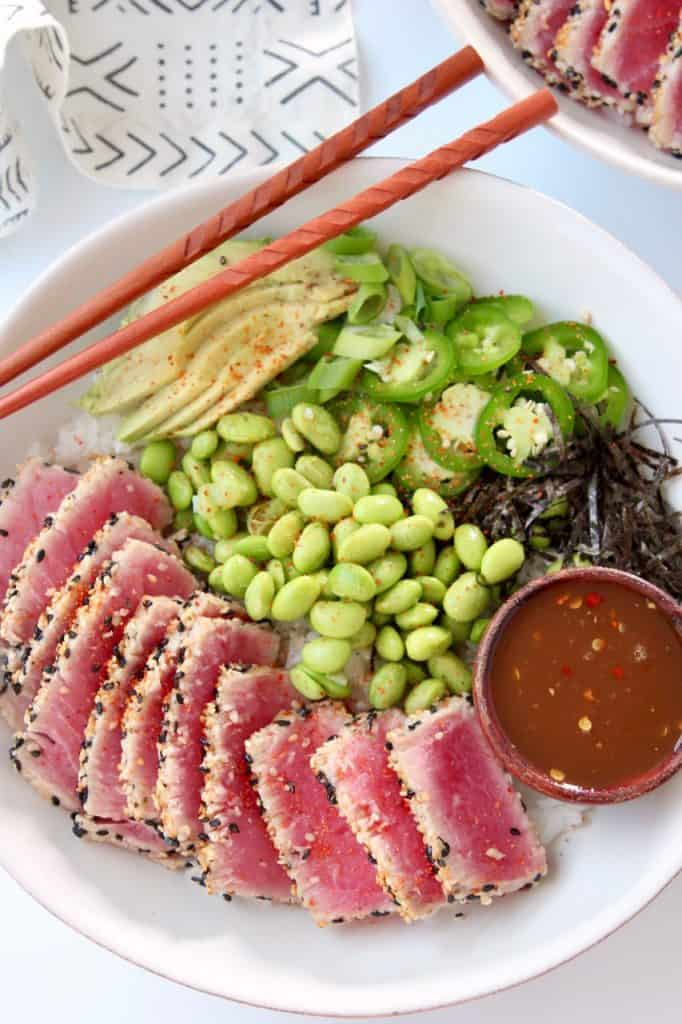 Sliced tuna in bowl with chopsticks and edamame
