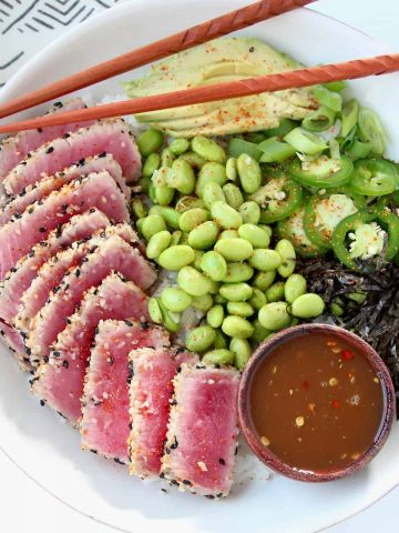 Overhead image of bowl with sesame crusted ahi tuna, edamame and sliced avocado