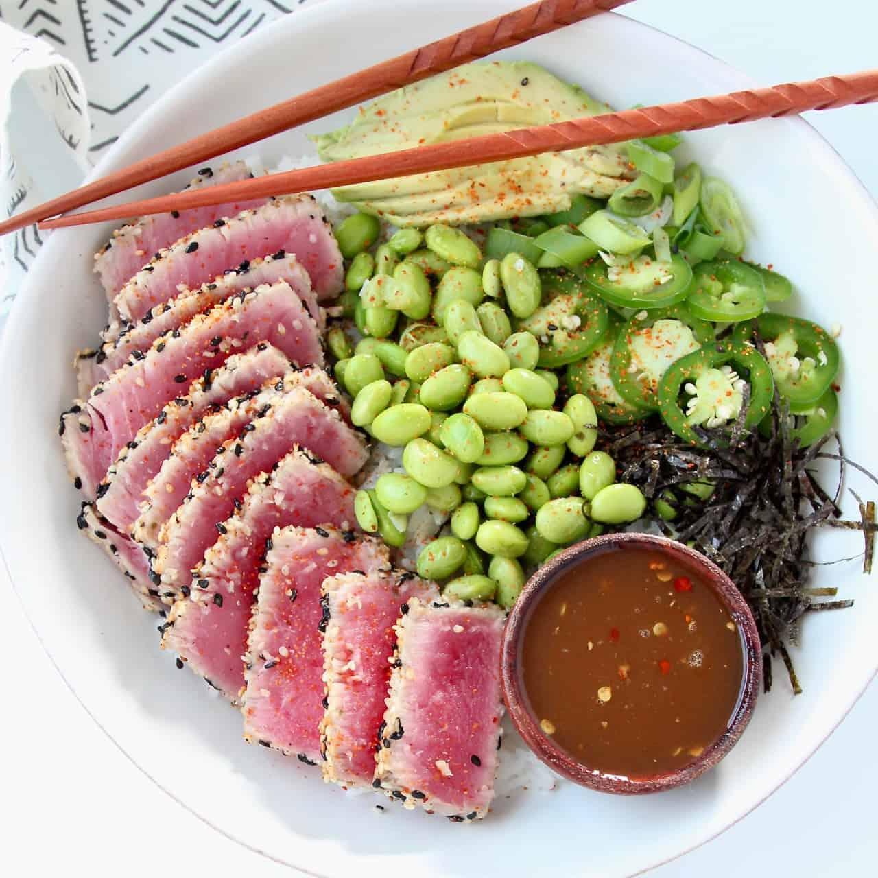 Overhead image of bowl with sesame crusted ahi tuna, edamame and sliced avocado
