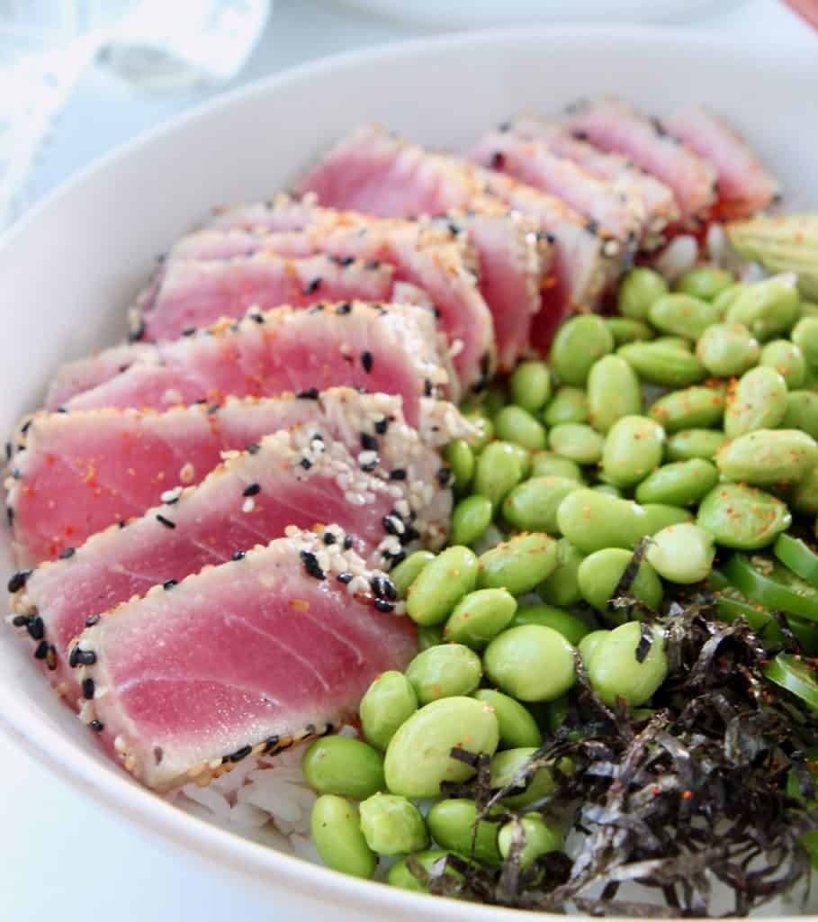 Sliced sesame seared tuna in bowl with edamame and shredded nori