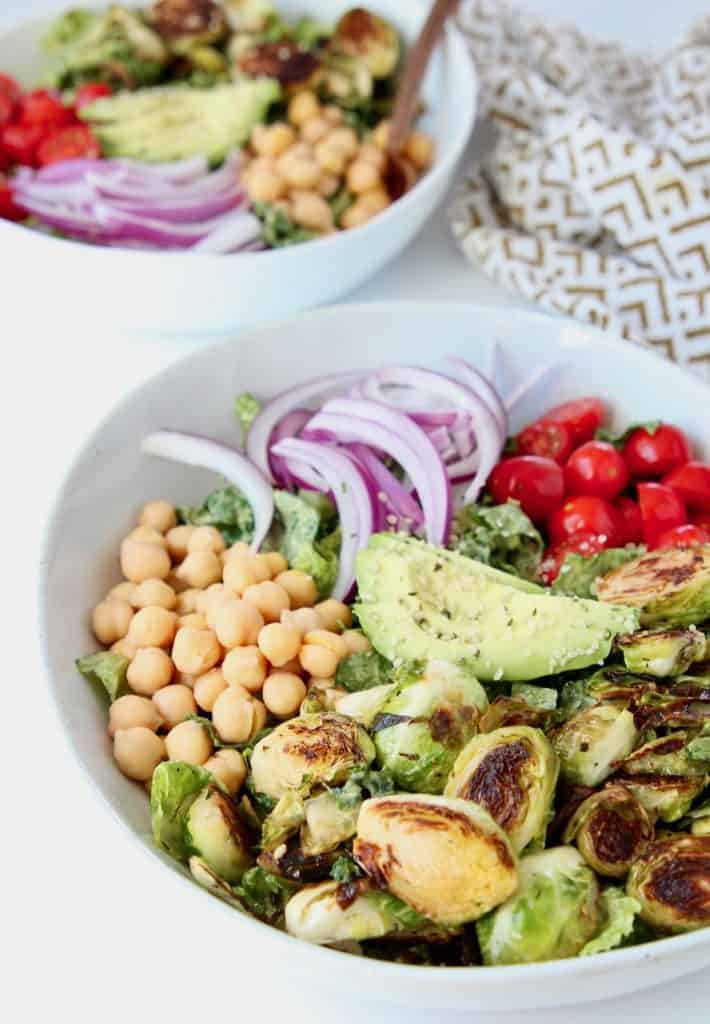 Salad with brussels sprouts, garbanzo beans, avocado and onions in bowl
