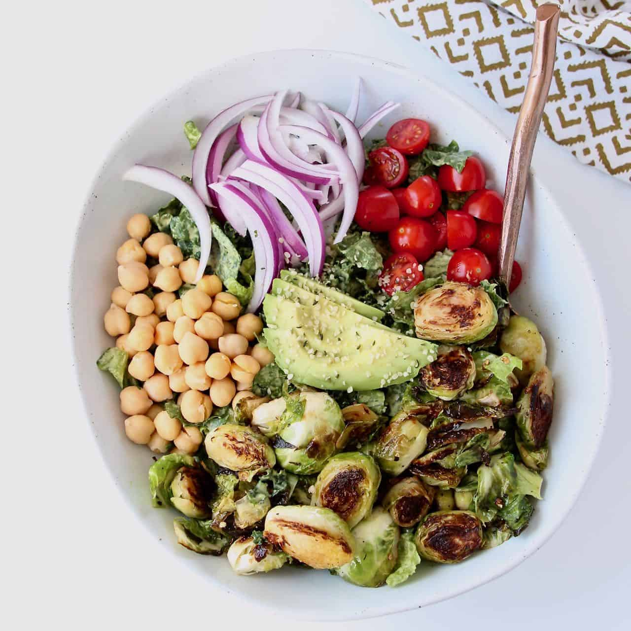 Overhead image of salad in bowl with roasted brussels sprouts, tomatoes and avocado