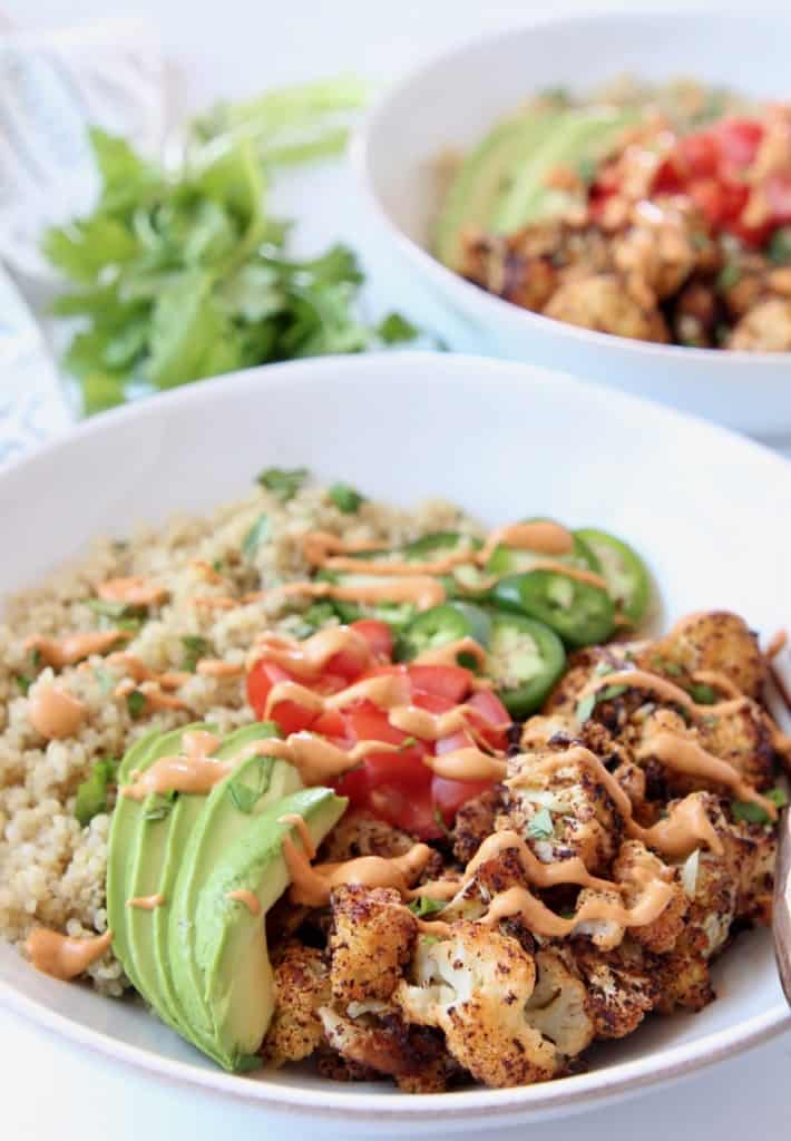 Roasted cauliflower in bowl with creamy chipotle sauce and sliced avocado