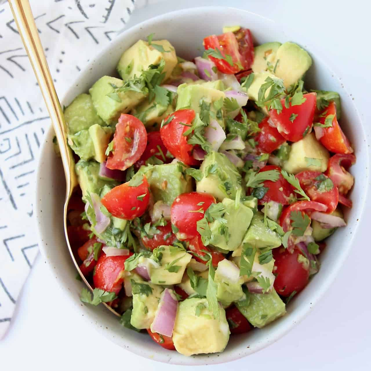 Avocado and tomato salsa in bowl with gold spoon