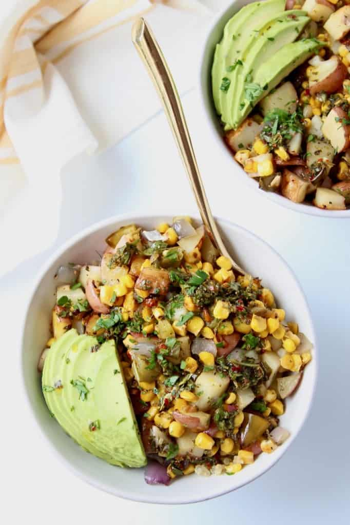 Overhead image of bowls with grilled vegetables and sliced avocado