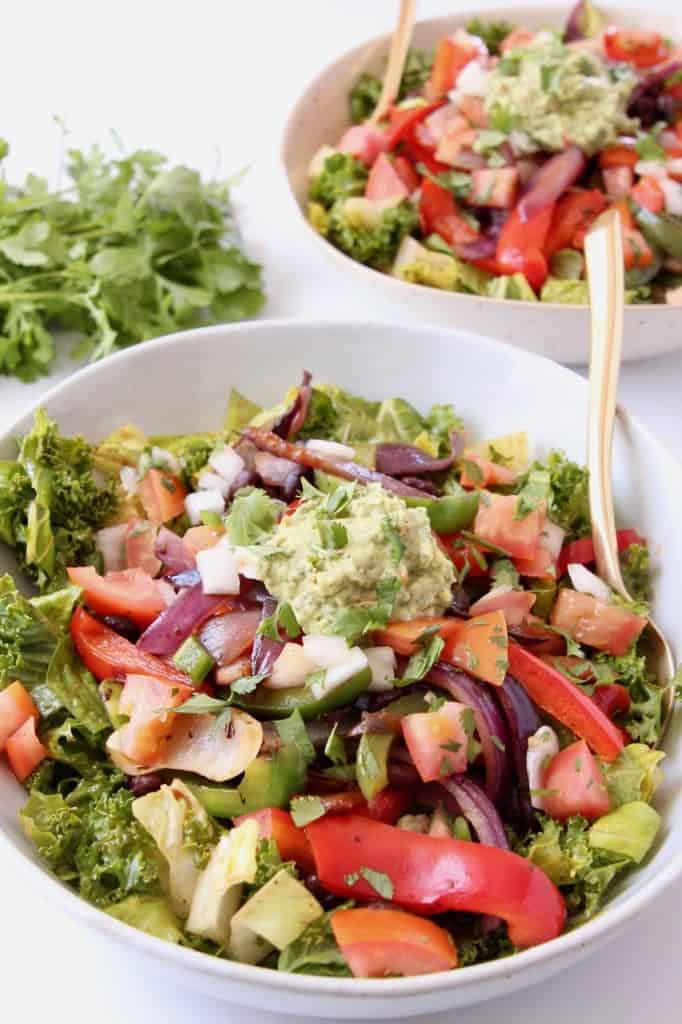 Fajita salad in bowls topped with guacamole
