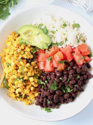 Overhead image of bowl filled with black beans, corn, diced tomatoes, avocado and quinoa