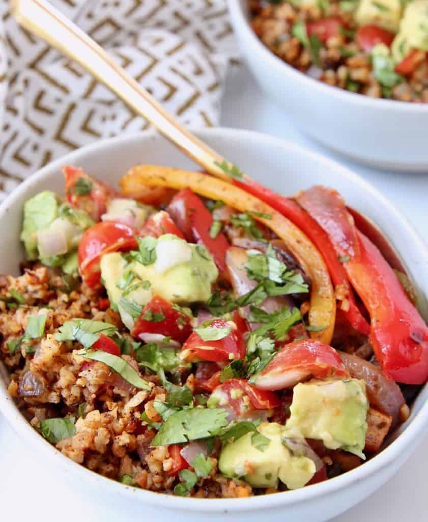 Bell pepper fajitas in bowl with avocado and roasted cauliflower rice