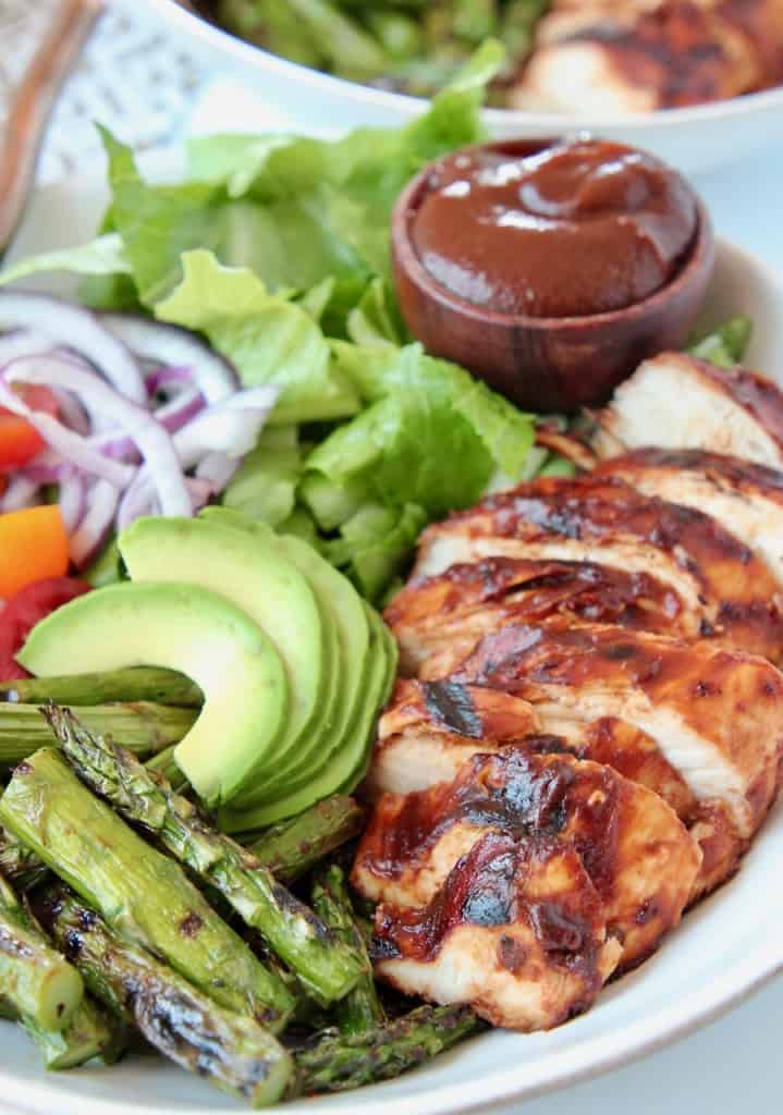 Sliced bbq chicken in bowl with avocado, asparagus and bbq sauce