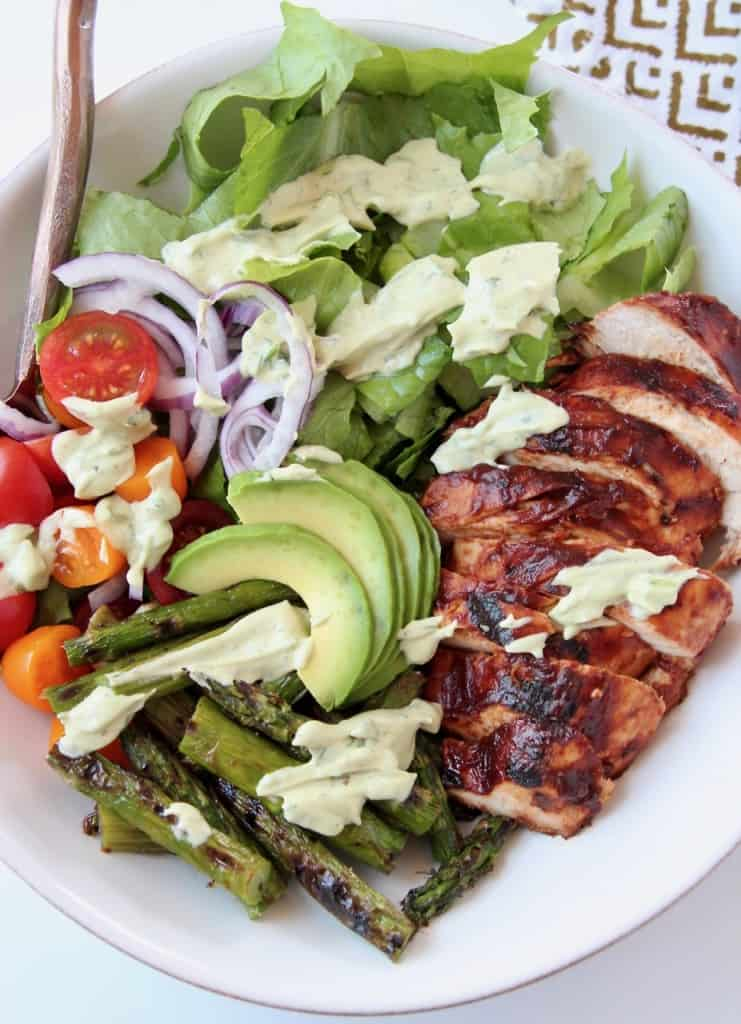 Sliced bbq chicken in bowl with greens, avocado and asparagus