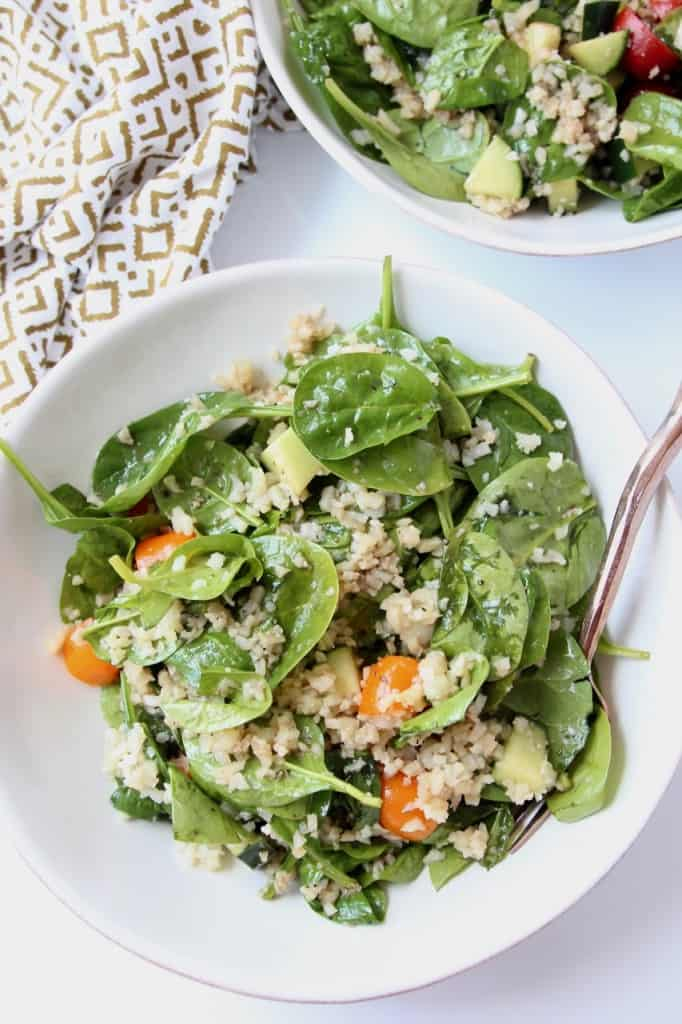 Overhead image of spinach salad in bowls with fork