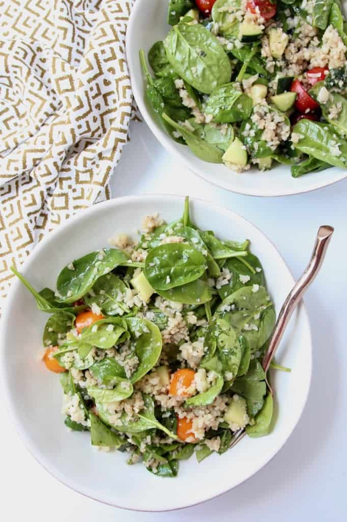 Overhead image of spinach salad in two bowls with forks