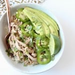 Overhead image of pulled pork in bowl with avocado and jalapeno slices