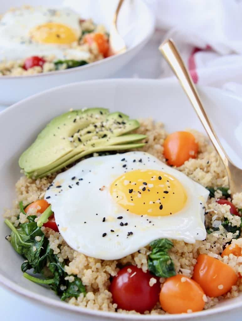Sunny side up egg in bowl with quinoa, tomatoes, spinach and avocado