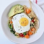 Overhead image of sunny side up egg in bowl with gold fork, sliced avocado and tomatoes