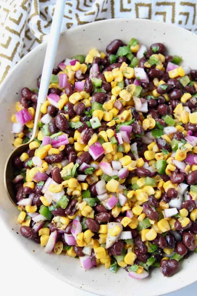 Overhead image of black bean corn salsa in bowl with spoon