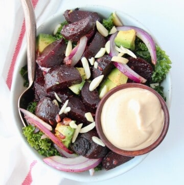 Overhead image of kale beet salad in bowl with side of tahini dressing