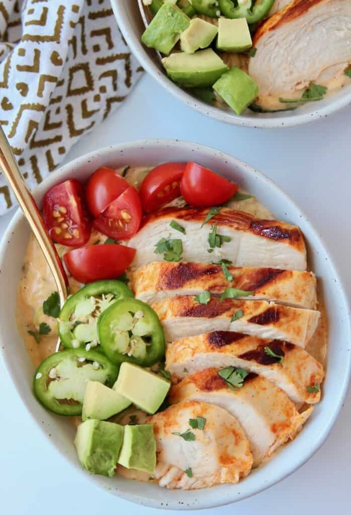 Sliced buffalo chicken in bowl with diced veggies