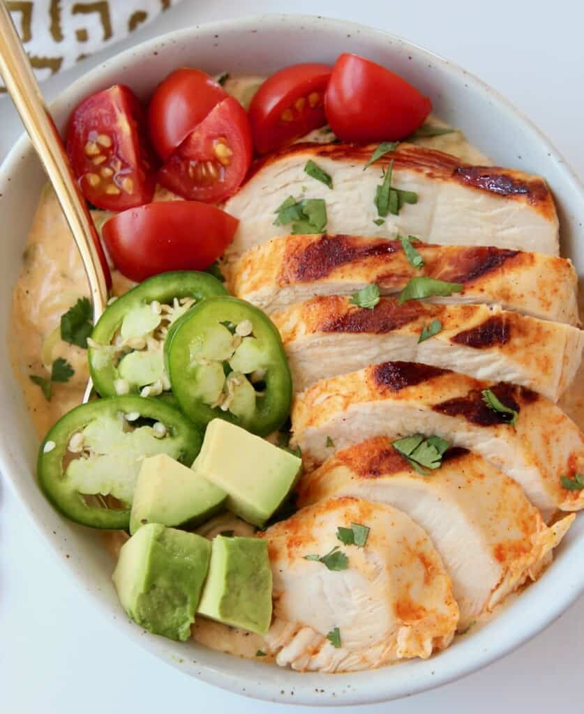 Overhead image of sliced chicken in bowl with diced vegetables