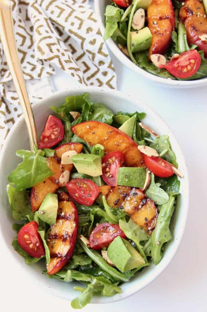 Overhead image of grilled peach salad in bowl with gold fork